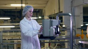 Food factory worker controls a conveyor, using a machine. stock video
