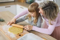 Young family making cookies at home. food, family, christmas, hapiness and people concept - smiling family making a. Food, family, christmas, hapiness and people Stock Photography