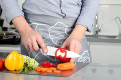 Food, family, cooking and people concept - Man chopping paprika on cutting board with knife in kitchen.  stock photo