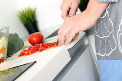 Food, family, cooking and people concept - Man chopping paprika on cutting board with knife in kitchen.  stock image
