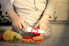 Food, family, cooking and people concept - Man chopping paprika on cutting board with knife in kitchen Stock Photography
