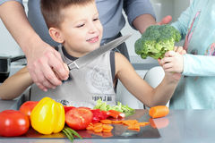 Food, family, cooking and people concept - Man chopping paprika on cutting board with knife in kitchen with son and daughter stock image