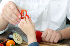 Food, family, cooking and people concept - Man giving paprika to the daughter royalty free stock photography