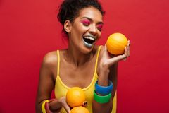 Food fashion photo of joyful mixed-race woman with colorful make. Up having fun holding lots of ripe oranges in hands isolated over red wall royalty free stock images