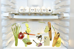 Food Fight. Healthy food battling unhealthy food for nutritious refrigerator dominance under the watchful eye of the neutral eggs Royalty Free Stock Photography