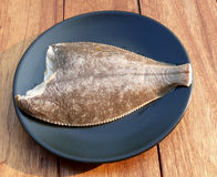 Food fish. Freshly caught plaice before cooking, lying on a black plate Royalty Free Stock Image