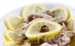 Food fish in oil. An appetizing food fish in oil adorned with lemons and olives Stock Photography