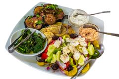 A food flat lay of traditional greek salad, black olives, sweet bell pepper, fried sliced potatoes, fried sliced eggplant, braised. Greens, sauces in the glass stock photography