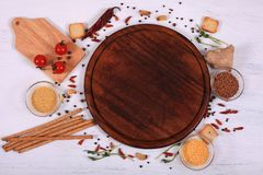 Food frame around brown round cutting board on white wooden table. stock photo