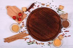 Food frame around brown round cutting board on white wooden table. stock photos