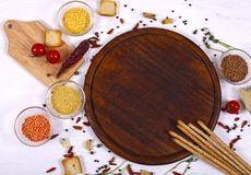 Food frame around brown round cutting board on white wooden table. royalty free stock photo