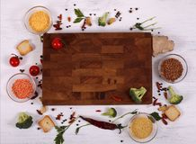 Food frame around empty brown cutting board on white wooden table. stock image