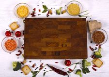 Food frame around empty brown cutting board on white wooden table. royalty free stock images