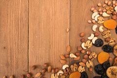 Food frame background with dried fruits and nuts: prunes, aprico. Ts, figs, hazelnuts, almond, cashew, walnut, peanuts over on old wooden background. Top view stock photos