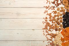 Food frame background with dried fruits and nuts: prunes, aprico. Ts, figs, hazelnuts, almond, cashew, walnut, peanuts over on white wooden background. Top view Royalty Free Stock Photo