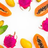 Food frame with banana, papaya, mango and dragon fruits on white background. Flat lay. Top view. stock photography