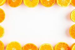Food frame of halves of mandarin orange on white background with Stock Images