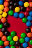 Frame of multicolor candy with a free space on a red background. royalty free stock image