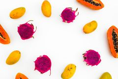 Food frame of papaya, mango and dragon fruits on white background. Flat lay. Top view. Tropical fruit concept royalty free stock images