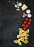 Food frame. Pasta ingredients. Cherry-tomatoes, pasta, garlic, basil, parmesan and spices on dark grunge backdrop, copy Royalty Free Stock Photos