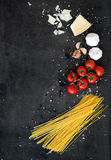 Food frame. Pasta ingredients. Cherry-tomatoes, spaghetti pasta, garlic, basil, parmesan and spices on dark grunge Royalty Free Stock Image