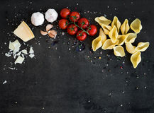 Food frame. Pasta ingredients on dark grunge backdrop, copy space Royalty Free Stock Photos