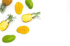 Food frame of sweet pineapple and mango fruits on white background. Flat lay, top view. Tropical concept stock photography