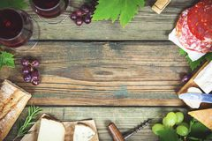 Food frame. Wine and snack set. With red wine in glasses, meat variety, bread, cheese and grape on rustic wooden background, top view, copy space in center royalty free stock image