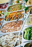 Food in a gastronomic capacity. Salads, marinated champignons with onion rings, sliced bacon, stewed eggplants with carrots, fresh cucumbers in gastronomic Stock Photography