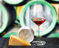 Glass of wine and cheese in winery Royalty Free Stock Photos