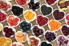 Food for Good health. Healthy super food for good health in heart shaped bowls with fruit, vegetable, pulses and grains on rustic  wood background. Superfood Royalty Free Stock Photos