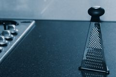 Food grater on kitchen counter. Dramatic still life of a food/cheese grater on a gray marble counter next to a range/stove Royalty Free Stock Image