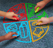 Food Groups. Nutrition and healthy lifestyle concept as a group of diverse children holding chalk drawing a pie chart diagram on asphalt with protein dairy Royalty Free Stock Images