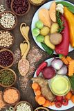 Food for Health and Well Being. Concept with fresh vegetables, herbs, dried pulses, himalayan salt and olive oil on old tin plate, a love spoon and wooden bowls Royalty Free Stock Image