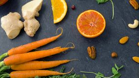 Close up of carrot, ginger, orange, lemon and nuts. Food and  healthy eating concept - close up of carrot, ginger root, orange, lemon and nuts on table top stock video footage