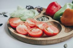 Food, healthy eating and nutrition concept - sliced pumpkin and other vegetables on wooden board. Fresh vegetables and greens on a. Wooden board. Eco style royalty free stock photos