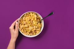 Food, healthy eating, people and diet concept - close up of woman eating muesli for breakfast over purple background stock images