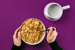 Food, healthy eating, people and diet concept - close up of woman eating muesli with milk for breakfast over purple stock image
