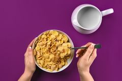 Food, healthy eating, people and diet concept - close up of woman eating muesli with milk for breakfast over purple stock photo