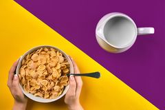 Food, healthy eating, people and diet concept - close up of woman eating muesli with milk for breakfast over purple and stock photo