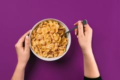 Food, healthy eating, people and diet concept - close up of woman eating muesli for breakfast over purple background royalty free stock photos