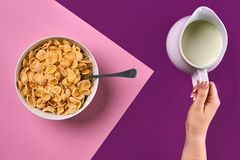Food, healthy eating, people and diet concept - close up of woman eating muesli with milk for breakfast over purple and royalty free stock photography