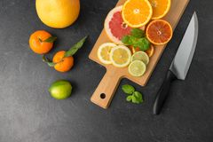 Close up of fruits and knife on slate table top royalty free stock image