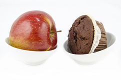 Food - Healthy versus unhealthy. Food - Healthy eating versus unhealthy eating- Apple or muffin Stock Photography