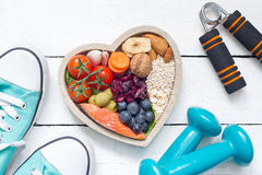 Food in heart and dumbbells fitness abstract healthy lifestyle concept. On white boards royalty free stock images