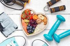 Food in heart and dumbbells fitness abstract healthy lifestyle concept. On white boards