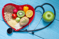 Food on heart plate with stethoscope cardiology concept Stock Photos