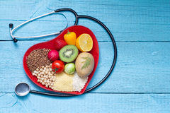 Food on heart plate with stethoscope cardiology concept Stock Photo