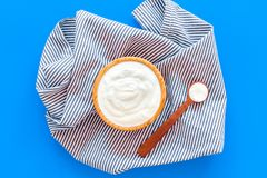 Food helps digestion. Greek yogurt in brown bowl near spoon on blue tablecloth, blue background top view.  royalty free stock images