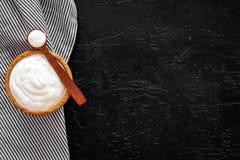 Food helps digestion. Greek yogurt in brown bowl near spoon on blue tablecloth, black background top view copy space. Food helps digestion. Greek yogurt in brown royalty free stock photo